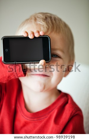 small 3 year old toddler boy holding his media player with empty screen in his hand - stock photo