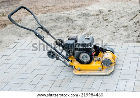Small yellow compactor standing on new gray  pavement - stock photo