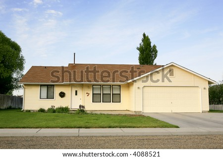 small yellow house with green grass out front
