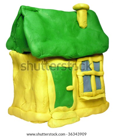 small yellow house with green roof maded from plastiline - stock photo