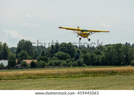 Small yellow tow plane landing on a grassy airfield.
