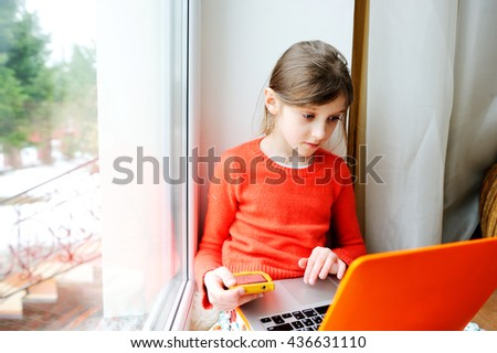 Small young brunette caucasian girl wearing colorful clothes, sitting near the window and using a laptop computer and phone - stock photo