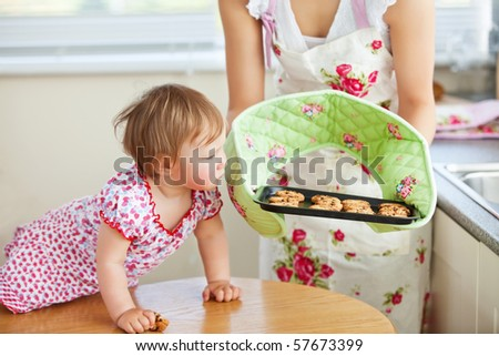 Small young girl looking at cookie in the kitchen - stock photo