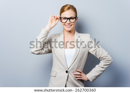 Smart and beautiful. Confident young businesswoman adjusting her eyewear and holding hand on hip while standing against grey background - stock photo