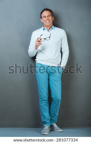 Smart and casual. Full length of cheerful mature man holding hand in pockets and smiling at camera while standing against grey background - stock photo