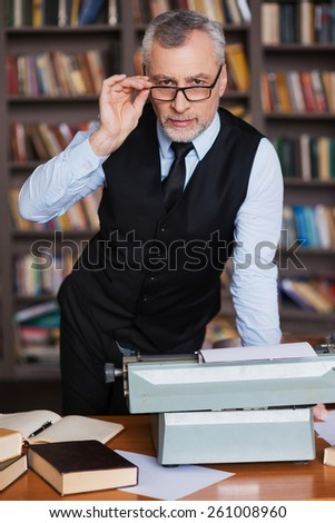Smart and confident. Confident grey hair senior man in formalwear leaning at the table with typewriter on it and bookshelf in the background - stock photo