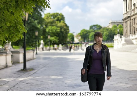Smart and confident young woman walking through urban area beside a public park. - stock photo