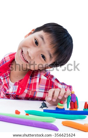 Smart asian boy playing and creating toys from play dough. Child smiling and show his works from clay, on white background. Strengthen the imagination of child - stock photo