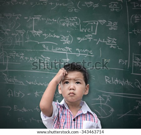 Smart Asian boy thinking with a blackboard in the background