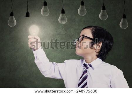 Smart asian child holding a lit bulb under lamps - stock photo