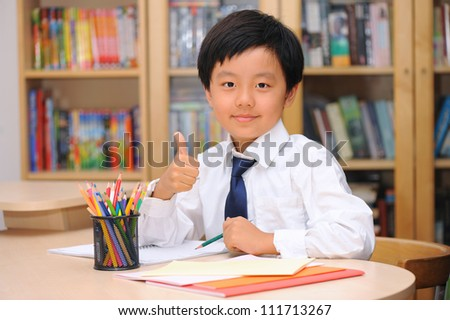 Smart Asian schoolboy wearing white shirt and tie sitting at a desk with thumbs up