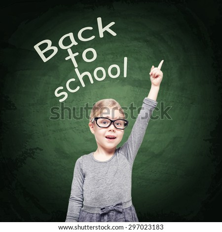 Smart beautiful little girl in glasses on the chalkboard background