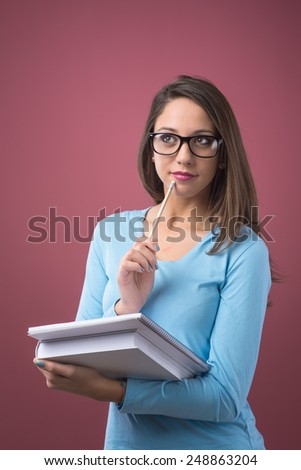 Smart beautiful student girl with glasses holding textbooks