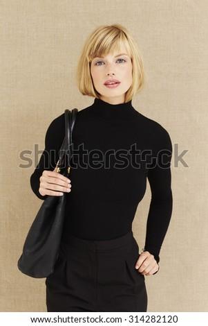Smart blond businesswoman in black, portrait - stock photo