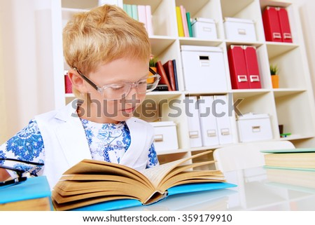Smart boy absorbed in reading a book. Education.  - stock photo