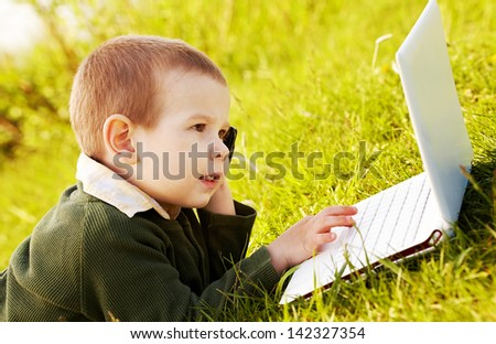 Smart boy lying on green grass and looking at laptop - stock photo