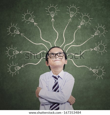 Smart boy thinking with many ideas on the classroom - stock photo