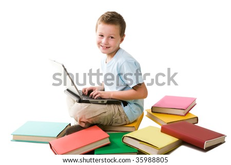 Smart boy typing on laptop and looking at camera over white background