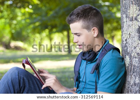 Smart boy using a tablet computer outdoors - stock photo
