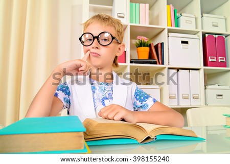 Smart boy wearing glasses sitting at the desk and looking at the camera with surprise. Education.