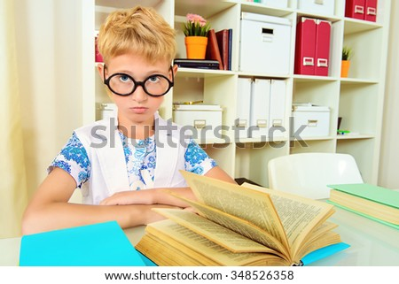 Smart boy wearing glasses sitting at the desk and seriously looking at the camera. Education.  - stock photo