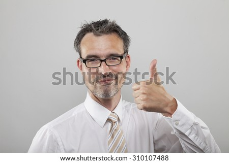 Smart business man holds thumb up - stock photo