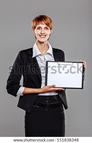 Smart business woman holding a clipboard isolated on grey - stock photo