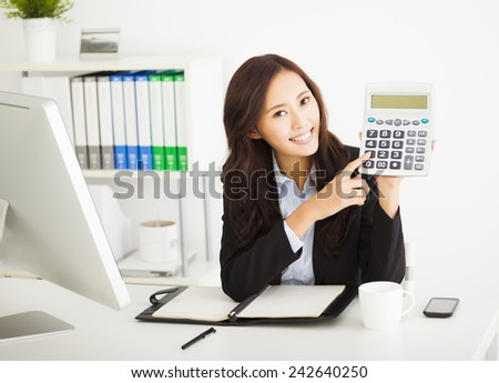 smart business woman showing the calculator in office - stock photo