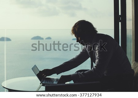 Smart businessman is working on laptop on the tropical islands background. Artistic toning. - stock photo