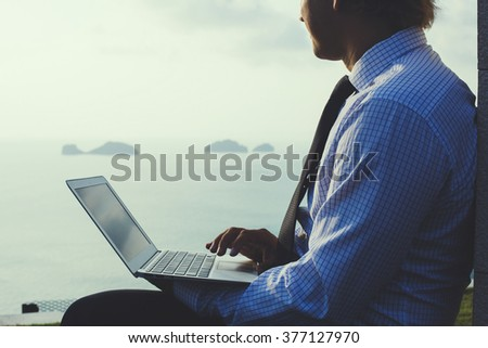 Smart businessman is working on laptop on the tropical islands background. Artistic toning.