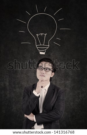Smart businessman looking for ideas on lightbulb background