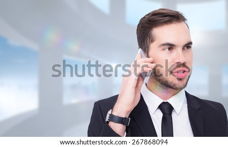 Smart businessman speaking on the phone against bright white room with windows