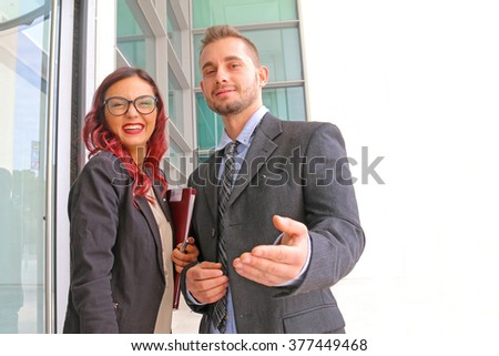 smart businessman with cheerful staff - young office executive introducing smiling office girl to a customer - view from customer's side - stock photo