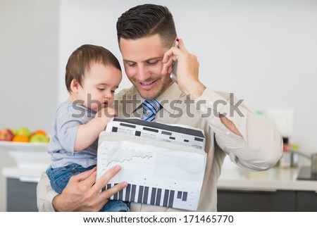 Smart businessman with documents carrying baby boy while on call at home - stock photo
