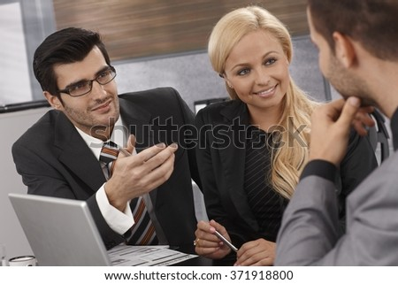 Smart businesspeople having meeting, talking, smiling. - stock photo