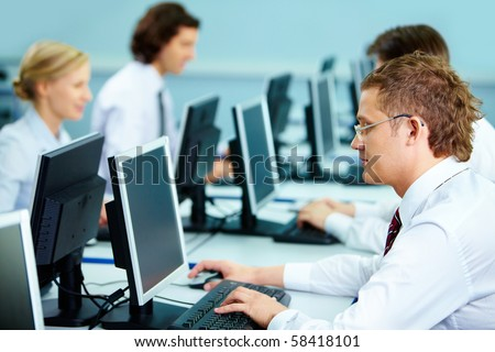 Smart businesspeople typing at workplaces in computer room - stock photo