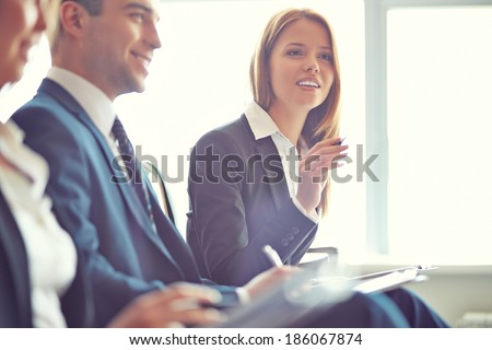Smart businesswoman asking question at seminar with her colleagues near by - stock photo