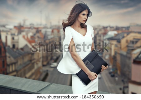 Smart businesswoman on the roof of the building - stock photo