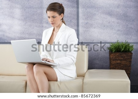 Smart businesswoman sitting on sofa in office lobby working on laptop computer.?