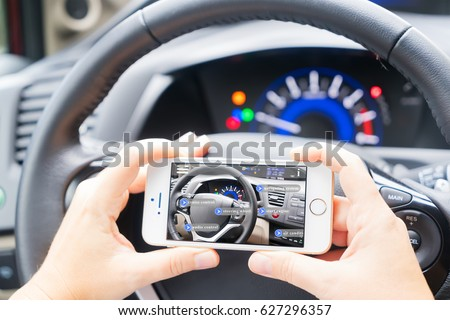 smart car concept driving wheel and hands holding phone with