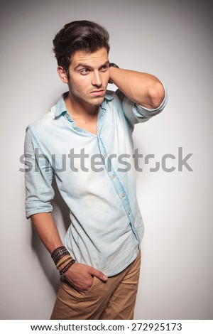 Smart casual man posing with his hand behind his neck while holding one hand in his pocket.