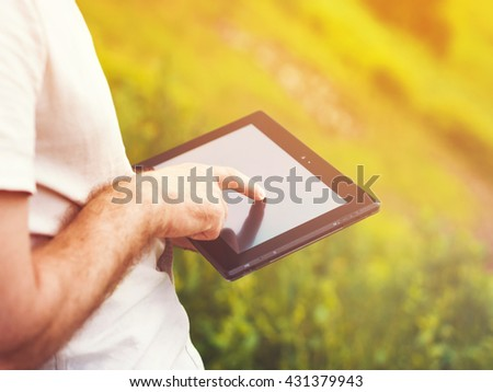 Smart casual man with digital tablet outdoors, close up. Focus on finger. Sunkissed effect with sunflares. Modern remote work concept.