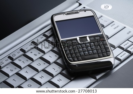 smart cell phone on a silver laptop - stock photo
