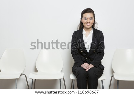 Smart Chinese business woman waiting for a job interview. Sitting on a row of chairs.