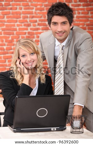Smart couple with a laptop computer and cellphone - stock photo