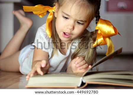 Smart cute kid girl with yellow bows lying on the floor and reading a book attentively, seriously and concentrated, indoor portrait, school and education concept - stock photo