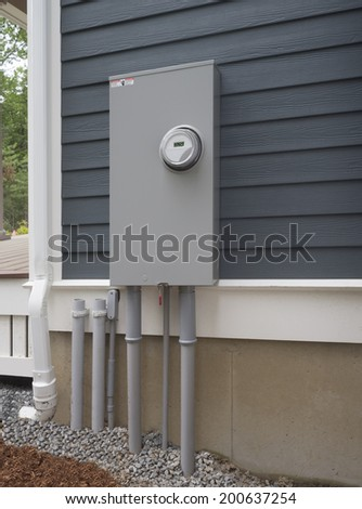 Smart digital electric utility meter and panel on new house - stock photo