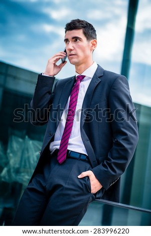 Smart dressed man talking in phone outdoors in front of office building