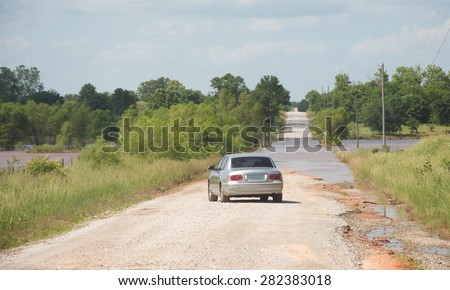 Smart driver backing out to turn around from a flood covered road to stay safe - stock photo
