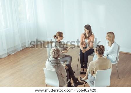Smart elderly psychotherapist talking with her patients - stock photo